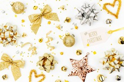 Christmas decorations, bows, stars,  bells in gold colors on white background with empty copy space for text. Holiday and celebration. Flat lay, top view