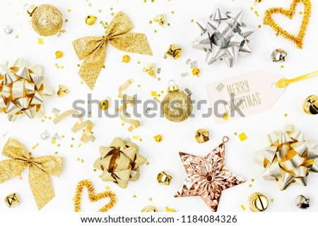 Christmas decorations, bows, stars,  bells in gold colors on white background with empty copy space for text. Holiday and celebration. Flat lay, top view #1184084326