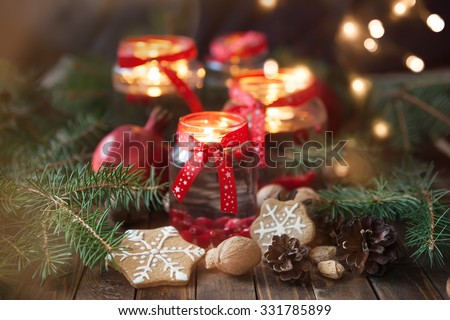 Stock Photo Christmas decorations. Candles in glass jars with fir  and gingerbread cookies