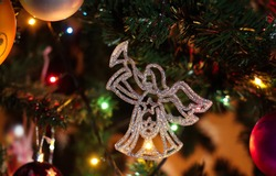 Christmas decorations. Christmas tree branches with an angel, balls, Christmas decorations and festive sparkle lights.