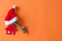 Christmas decorations: decorative house with key to the lock and Santa hat on red paper background, concept of finance and housing loans