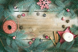 Christmas decorations: fur-tree branches, colorful glass balls, a candle, red glittering snowflake, cinnamon sticks and anise stars on a rough wooden background with a copy space