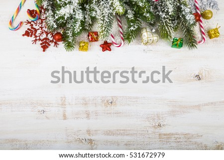 Christmas decorations, gifts and fir branches in the snow on a wooden table. Christmas border closeup. #531672979