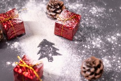 Christmas decorations, gifts and pine cones in the snow and the silhouette of a Christmas tree. Christmas mood. Flatly photo.