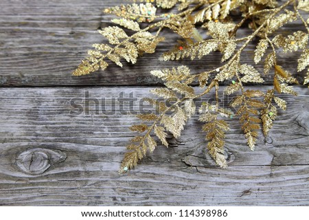 Christmas decorations: golden twig on a wooden background