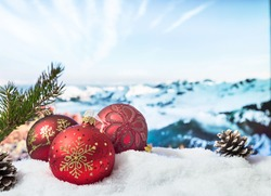 Christmas decorations in a snowdrift in front of snowy mountains. Winter Christmas background.