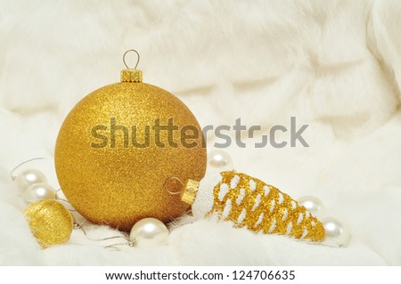 Christmas decorations in gold and white colors: cones and balls on a white fur closeup