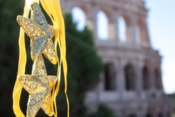 Christmas decorations in the form of gold stars on the background of the Colosseum, Rome. Christmas and New Year in Italy