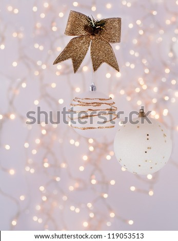 Christmas decorations in the form of white with gold balls on the background of an abstract background - bokeh.