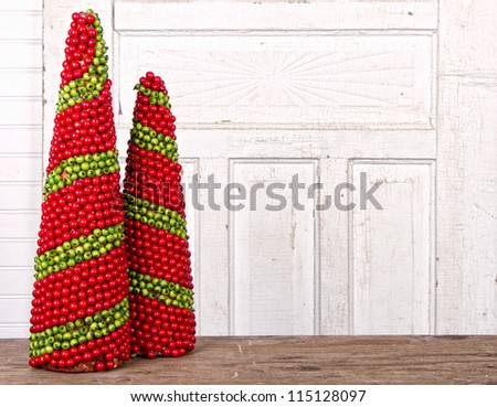 Christmas decorations made of berries in the shape of a cone with antique wooded panels for background