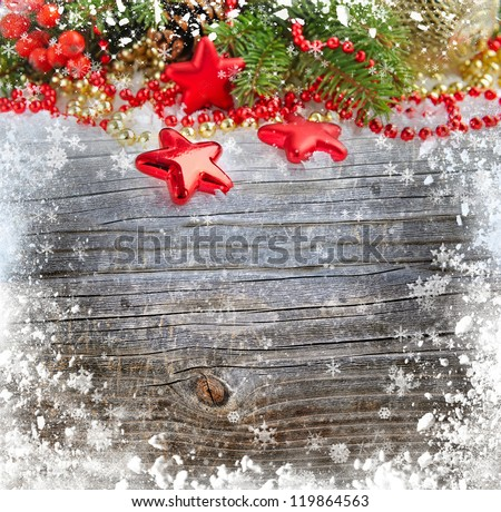 Christmas decorations of bauble are with the branches of fir on a snowbound wooden background