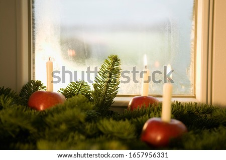 Christmas decorations of candles in apples near window