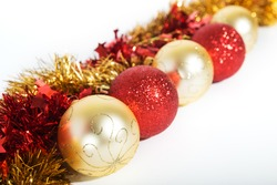 Christmas decorations ofred and golden color on a white background - balls and tinsel