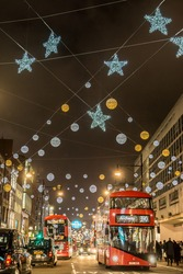 Christmas decorations on Oxford Street, London with red bus.