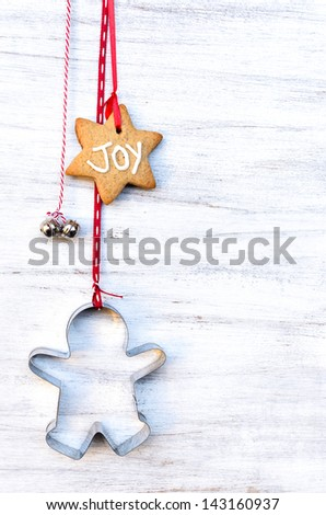 Christmas decorations on wooden rustic white background, gingerbread star, cookie cutter and bells - stock photo