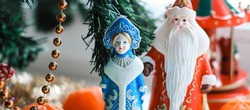 Christmas decorations (Russian Santa Claus and Snow Maiden) standing near with Christmas tree. New Year, holiday banner.