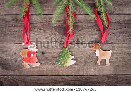 christmas decorations ( santa claus, moose and Christmas tree) hanging over wooden background - stock photo