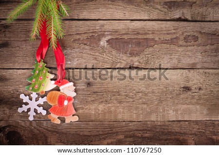 christmas decorations ( santa claus, snowflake and Christmas tree) hanging over wooden background