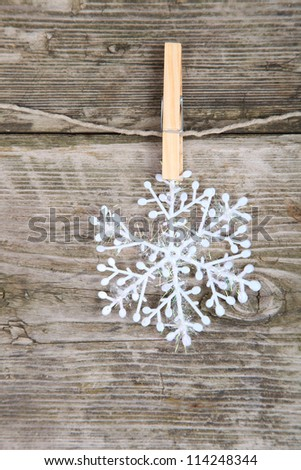 Christmas decorations, snowflake hanging over wooden background - stock photo