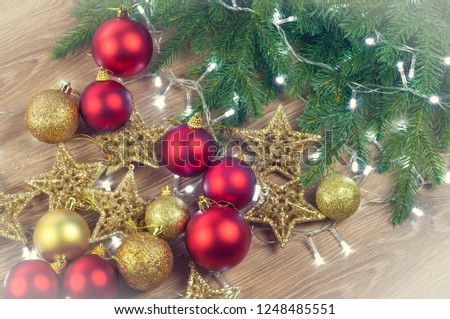 Christmas decorations with fir branches on wooden background, balls and stars, gold and red #1248485551