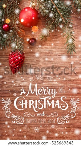 Christmas decorations with fir tree branch on wooden background with snow, blurred, sparking, glowing and text Merry Christmas and Happy New Year. Xmas card #525669343