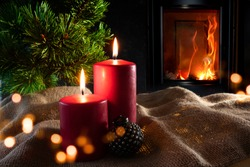 Christmas decorations with log fire and festive bokeh. Atmospheric christmas still life with fir tree and with candlelight on rustic linen sack. Space for your text.