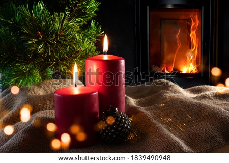 Photo of  Christmas decorations with log fire and festive bokeh. Atmospheric christmas still life with fir tree and with candlelight on rustic linen sack. Space for your text.