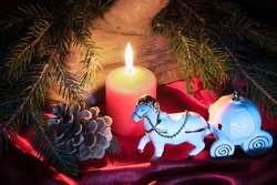 Christmas decorations with porcelain Cinderella toy carriage, horse, bright light burning candle and green fir tree branches. Fabulous magic style.