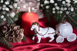Christmas decorations with porcelain Cinderella toy carriage, horse, candle burning, cone and green fir tree branches on wooden and red fabric background. Beautiful bokeh