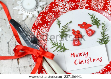 Christmas decorations with red plate snowflake ornament, cutlery tied with red ribbon and pine branch with christmas toys
