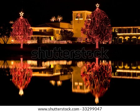 Christmas decorations with strands of lights reflected in a lake at night.