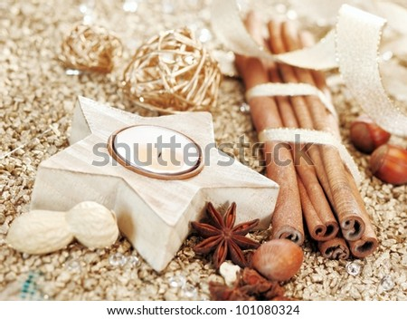 Christmas decorative background with a star shaped candle and mixture of dried spices and nuts