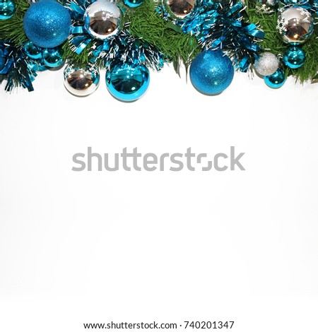 Christmas decorative frame. Branches of Christmas trees, silver and blue balls and a mishap isolated on a white background #740201347