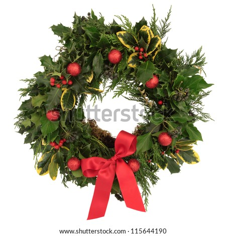 Christmas decorative wreath of holly, ivy, cedar cypress leaf sprigs and red bauble decorations with bow over white background.