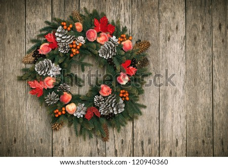 Christmas Decorative Wreath with Pine Cones, Berries, Apples, Red Leafs on Wooden Background