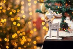 Christmas deer toy with jingle bells on the piano with beautiful christmas lights on the background. Christmas time