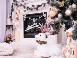 Christmas deer under New Year Tree with gifts, presents. Christmas stocking over fireplace decor, New Year's card scenery. Snowmans with stars and candels. New Year concept.