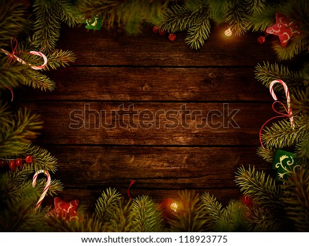 Christmas design - Merry Christmas. Xmas wreath card with with copyspace on wooden background. Christmas ornaments on wood with candy and ribbons.