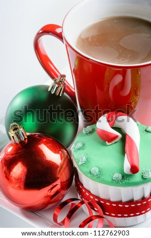 Christmas dessert cupcake with candy cane icing decoration red green xmas baubles ribbons and hot chocolate