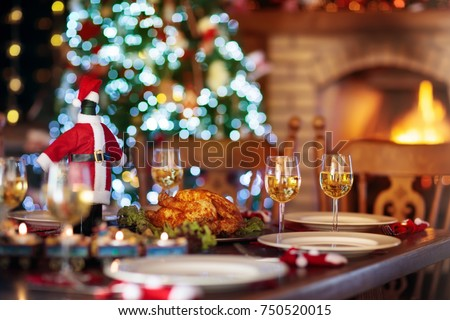 Christmas dinner at fireplace and decorated Xmas tree. Dish with roasted turkey, salad and baked potato served for festive family meal. Wine bottle with Santa hat. Open fire in stone oven. #750520015