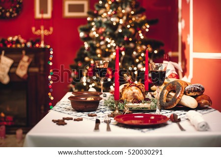 Christmas dinner by candlelight, table setting. Thanksgiving table with baked turkey in a decorated room with a Christmas tree. #520030291