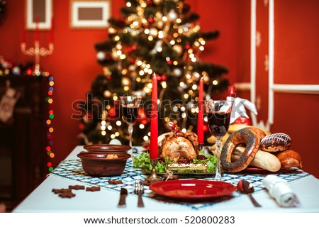 Christmas dinner by candlelight, table setting. Thanksgiving table with baked turkey in a decorated room with a Christmas tree.