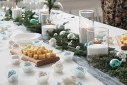christmas dinner, Christmas table decoration, a burning candle, tangerines on the table, banquet table with glasses and snacks, banquet, decoration red deer on the table, beautiful