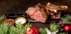 Christmas dinner for two. Baked beef on the bone with spices on a meat knife with Christmas tree and Christmas tree decorations