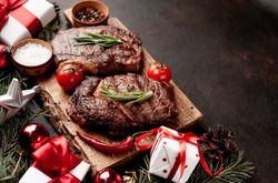 Christmas dinner for two, grilled beef steak, ribeye, greens and spices on a stone table with a Christmas tree and New Year's toys with copy space