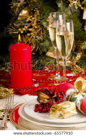 Christmas dinner place setting with Christmas table cloth, plates, knife and fork, small presents, candles, christmas decorations champagne and wine glass.