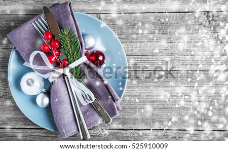 Christmas dinner plate decoration with xmas ornaments on old wood background. Merry christmas card. Winter holiday theme. Happy New Year. Space for text. Glitter snow effect