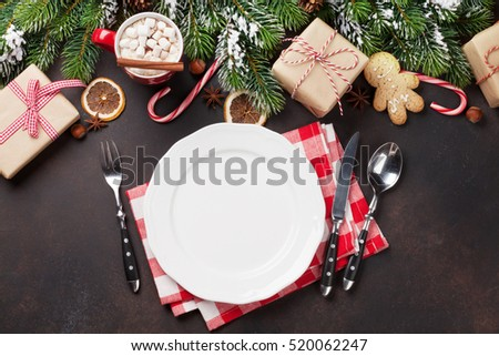 Christmas dinner plate, silverware, fir tree, gift boxes, hot chocolate. Top view with copy space