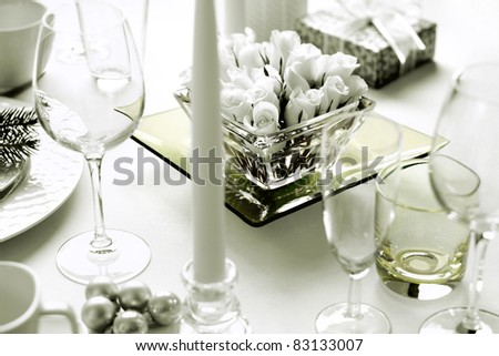 Christmas dinner table setting with roses and present