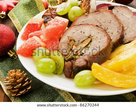 Christmas dinner turkey roulade with fruits and vegetables. Shallow dof.